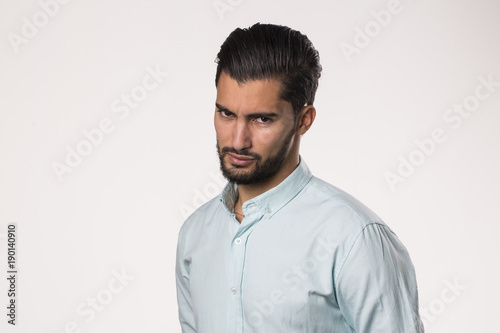 severe and harsh face expression of handsome young male isolated on white backgr Wallpaper Mural