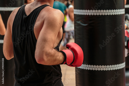 Photo  Fitness and Boxing Workout: Boy with Red Gloves and Black Punching Bag