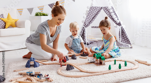 Foto  family mother and children play a toy railway in   playroom