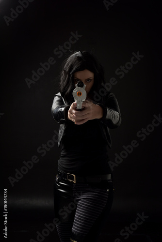 portrait of black haired girl wearing leather clothes, moody lighting on black background Tablou Canvas