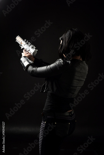 Fotografie, Tablou portrait of black haired girl wearing leather clothes, moody lighting on black background