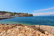 Rocky coast of Ionian Sea and houses on the hill in distance. Kassiopi village in Corfu. Greece