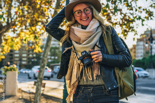 Spoed Foto op Canvas Boerderij Sunny day, autumn.Young woman tourist, photographer, hipster girl dressed in hat and eyeglasses,sits on bench on city street and takes photo.Vacation, travel,adventure, sightseeing.Blurred background.