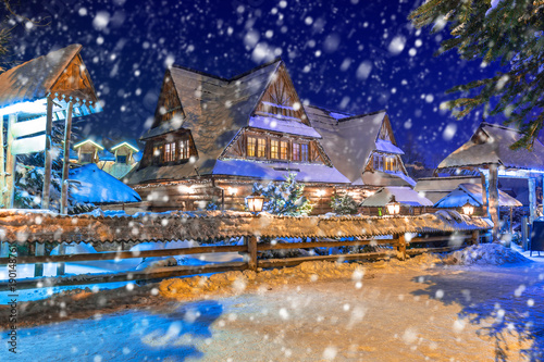 Wooden architecture of Zakopane on a cold winter night with falling snow, Poland
