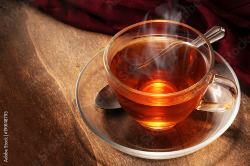 black tea freshly brewed in a glass cup, steaming hot drink on dark rustic wood, copy space