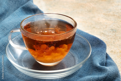 Foto op Plexiglas Thee freshly brewed black tea with a cream cloud in a glass cup, steaming hot drink on a blue napkin, copy space