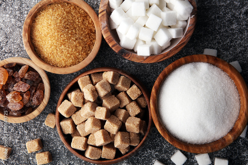 Leinwand Poster Various types of sugar, brown sugar and white on grey table