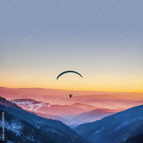 Spoed Fotobehang Luchtsport Parachuting in sunset light above mountains