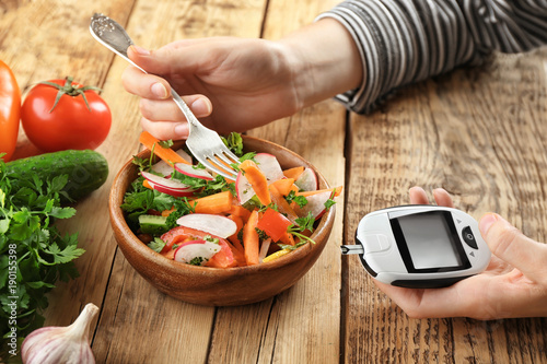Cuadros en Lienzo Woman holding digital glucometer while eating salad at table