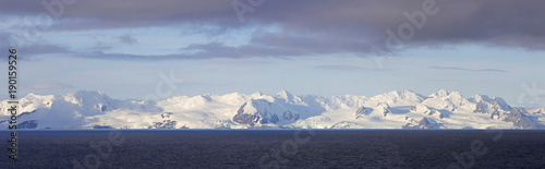 Photo Stands Antarctic Antarctica Snow Capped Mountains, four photo stitch Panoramic. Storm clouds above blue sky.