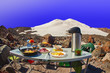 canvas print picture - Tourist breakfast. High mountain summit camp located on stony moraine of glacier against the background of high snowy peak under clear blue sky. Early morning.