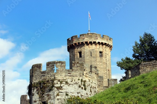 Tower and battlements of a medieval English castle on a grassy mound against blu Poster
