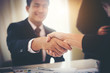Business people shaking hands while sitting at the working place, Finish success business good deals meeting