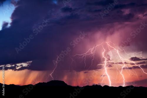 Fotografie, Obraz  Lightning strikes from a monsoon thunderstorm at sunset in the Arizona desert