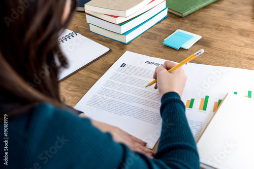 Photo Female college student reading information on paper, doing homework