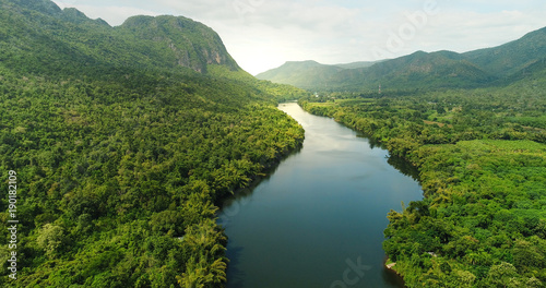 Staande foto Rivier Aerial view of river in tropical green forest with mountains in background