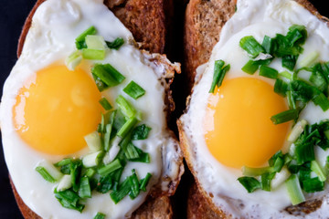 Fototapetatwo fried eggs on bread with spring green onion