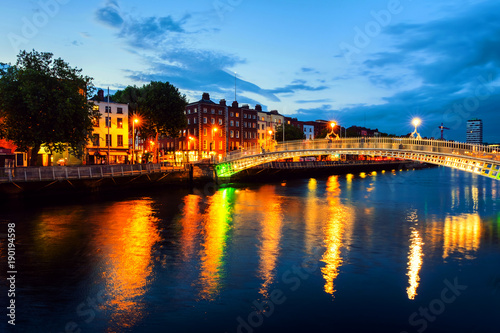 Stampa su Tela  Night view of famous illuminated Ha Penny Bridge in Dublin, Ireland