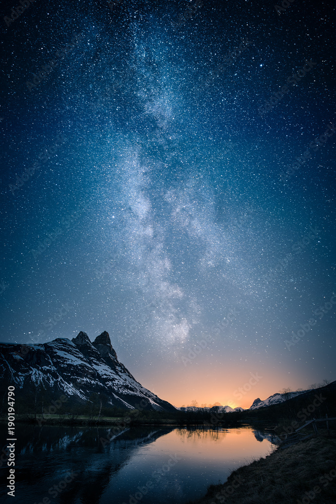 Fototapeta Beautiful view of milky way glowing on the sky with mountains and river and reflections of stars