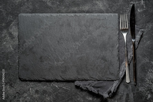black stone board with fork and knife on black textured cement background, top view vith copy space for your text