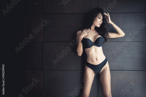 Asian adult sexy lady with big breast in black underwear on black wall background