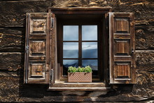 Beautiful Open Wooden Window Shutter With Flowers Reflecting Blue Sky On Wooden Log Cabin In Livigno, Italy
