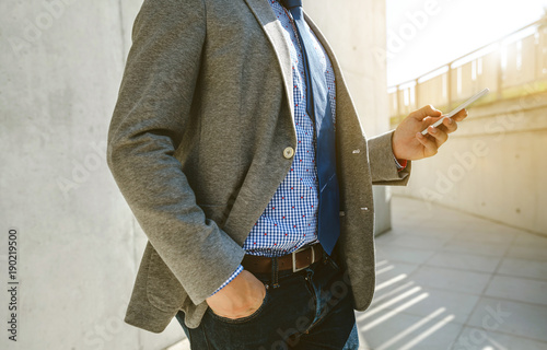 Unrecognizable businessman with cell phone in front of a concrete wall Canvas Print