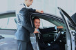 Young man choosing car at salon with help of consultant.