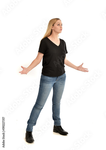 Fényképezés full length portrait of blonde girl wearing black shirt and jeans, standing pose isolated on a white background
