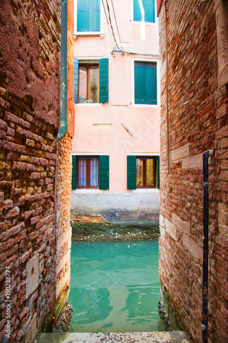 Poster Smal steegje The end of a narrow alley in Venice leading to a canal with windows on the opposite side.