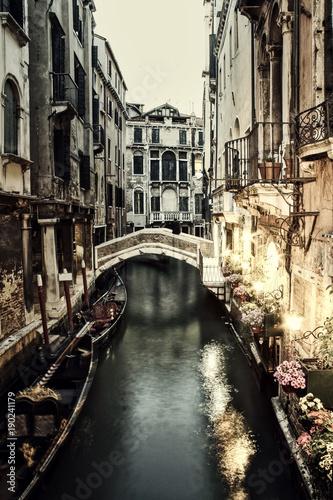 Fotografie, Obraz  A restaurant lit up at night along a Venice canal.