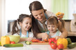 Mother with children preparing a vegetables salad in the kitchen