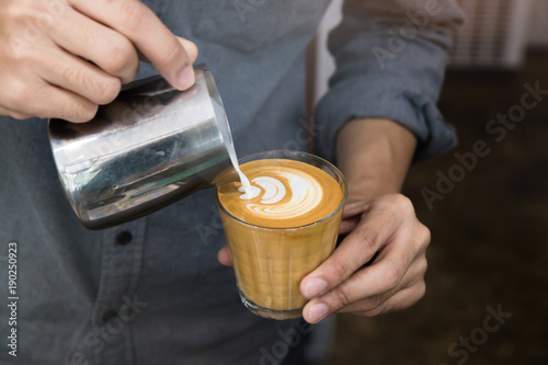 Fotografie, Obraz  Close-up of male barista hand holding and pouring hot milk for prepare latte art on piccolo latte cup of coffee