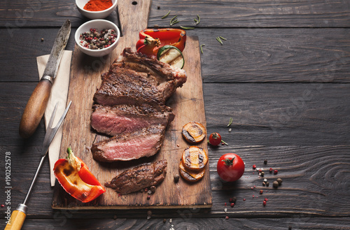 Foto op Canvas Vlees Grilled meat and vegetables on rustic wooden table