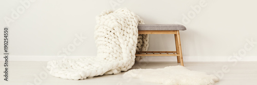 Obraz White knit blanket on stool - fototapety do salonu