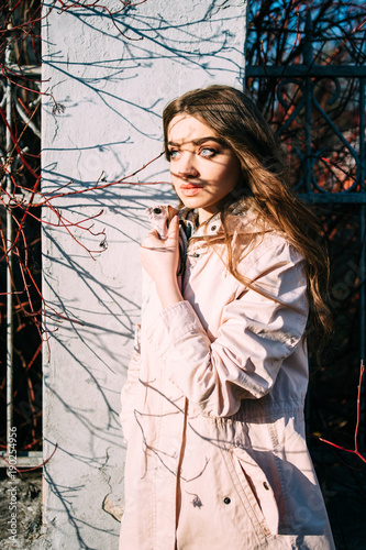 dd27bb5fb Stylish beautiful brunette woman in classical coat standing outdoor beyond  fence and posing for camera. Branches shadows falling at white wall and  cute ...