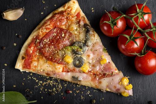 Kawałek włoskiej pizzy Capriciosa na ciemnym łupku z suszonym oregano
