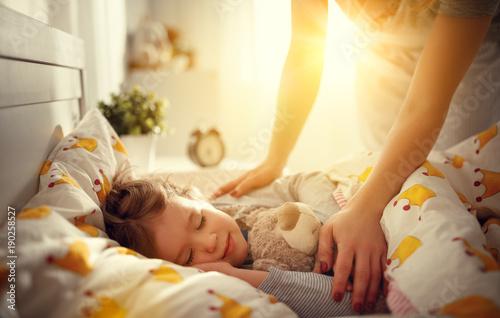 Obraz mother wakes up sleeping child daughter girl in morning. - fototapety do salonu
