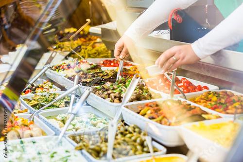 Fotografie, Obraz  Woman selling Meze appetizers in delicatessen store