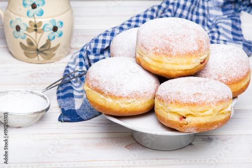 Tradycyjne polskie pączki z cukrem pudrem i nadzieniem na drewnianym tle, podawane w tłusty Czwartek