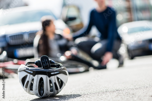 Photo Close-up of a bicycling helmet fallen down on the ground after accidental collis