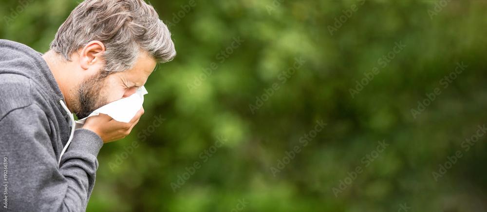 Fototapeta Mann mit Heuschnupfen muss in Taschentuch niesen