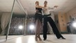 Young man and woman dancing and practicing Latin American dance in costumes in the Studio, slow motion, in action