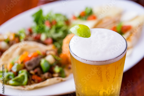 Slika na platnu Cold beer with lime wedge and Mexican food dish in beef tacos in background
