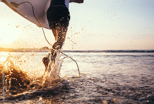 Closeup image water splashes from surfer's legs run in ocean with surfboard