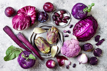 Raw Purple Vegetables Over Gray Concrete Background. Cabbage, Radicchio Salad, Olives, Kohlrabi, Carrot, Cauliflower, Onions, Artichoke, Beans, Potato, Plums. Top View, Flat Lay.