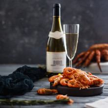 Seafood Shrimp. Close-up Of Ready-made Shrimps Lie In Plate, Dark Background. In Background, Crab Hairy, Bottle Of Champagne And Glass. Concept Grilled Dinner
