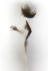 Sylwetka szczupłego, ludzkiego ciała kobiety, latające włosy, dłoń, palce.
