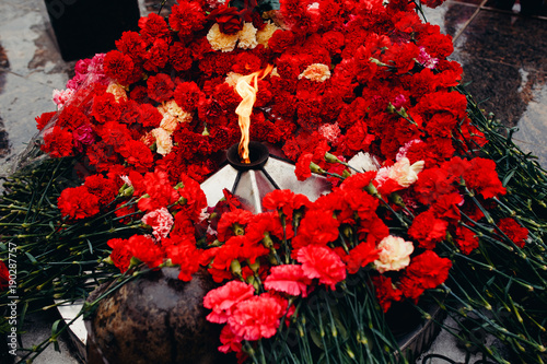 Fotografia  Background of red carnations, eternal fire, soldiers' helmets