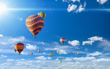 FototapetaColorful hot air balloons flying in blue sky with white clouds and bright sun light